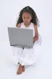 Una bella ragazza di sei anni con il computer portatile sopra bianco Fotografie Stock Libere da Diritti