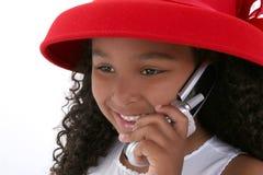 Una bella ragazza di sei anni in Red Hat con il cellulare Fotografia Stock Libera da Diritti