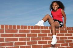 Una bella ragazza di sette anni sul muro di mattoni Immagine Stock