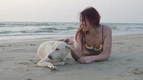Una bella ragazza e un cane bianco riposano sulla spiaggia un giorno di estate 4K video d archivio