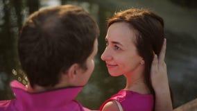 Una bella ragazza e un tipo stanno sedendo dal fiume al tramonto Data di una coppia amorosa all'aperto stock footage