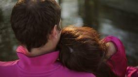 Una bella ragazza e un tipo stanno sedendo dal fiume al tramonto Data di una coppia amorosa all'aperto archivi video