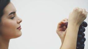 Una bella ragazza esile mangia i frutti sani Ritratto di una giovane donna graziosa che tiene un mazzo maturo dell'uva e una veri video d archivio