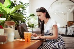 Una bella ragazza mora sorridente, vestita nello stile casuale, lavora duro in una caffetteria moderna Facciale messo a fuoco immagini stock