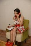Una bella ragazza mora sta annotando qualcosa mentre parlava dal telefono Fotografia Stock Libera da Diritti
