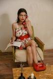 Una bella ragazza mora sta annotando qualcosa mentre parlava dal telefono Fotografie Stock Libere da Diritti