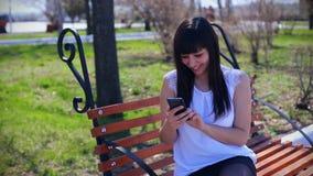 Una bella ragazza orientale in una blusa bianca, sedentesi in un parco su un banco, tiene uno smartphone ed è molta stock footage