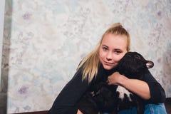 Una bella ragazza si siede e tiene molto piccolo cucciolo di un cane del bulldog francese immagini stock