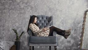 Una bella ragazza si siede su una poltrona molle in uno studio di arte ed esamina gli impianti dipinti dal truccatore Face archivi video
