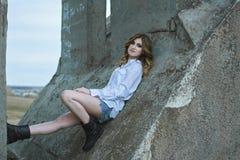 Una bella ragazza si siede su un vecchio ponte Fotografie Stock