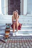 Una bella ragazza si siede sui punti, di estate nella città, chiamate sul telefono, vicino ad un pattino, un longboard, una tazza fotografie stock