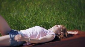 Una bella ragazza si trova su un banco e sui sogni di parco Goda del completamento della natura di playback lento archivi video