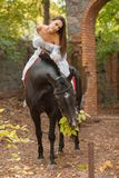 Una bella ragazza sta sedendosi su un cavallo mentre il cavallo sta mangiando il fogliame fotografia stock libera da diritti