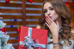 Una bella ragazza tiene un contenitore di regalo rosso ed invia un bacio dell'aria fotografia stock