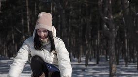 Una bella ragazza in un pino che il parco gode del tempo nevoso dell'inverno, lei getta allegro su un'bracciata di neve sopra la  video d archivio