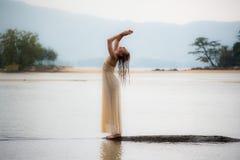 Una bella ragazza in un vestito bianco per sollevare h Fotografie Stock
