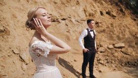 Una bella ragazza in un vestito bianco sta contro lo sfondo di una carriera sabbiosa Ha chiuso i suoi occhi e si è goduta di Stan archivi video