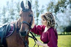 Una bella ragazza in un vestito da Borgogna ed in un cavallo marrone immagine stock libera da diritti