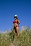 Una bella ragazza in un vestito di nuoto sta in un'alta erba Fotografia Stock