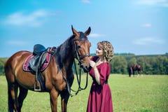 Una bella ragazza in un vestito ed in un cavallo lunghi fotografia stock