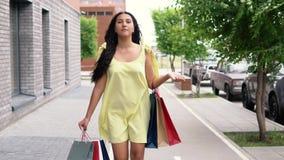 Una bella ragazza in un vestito giallo sta camminando giù la via dopo la compera avendo un buon umore Movimento lento stock footage