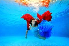 Una bella ragazza in un vestito nuota underwater nello stagno, giochi con un panno rosso e blu e sguardi alla macchina fotografic Fotografie Stock