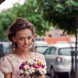 Una bella ragazza in vestito da estate con un mazzo di fiori i Immagine Stock Libera da Diritti