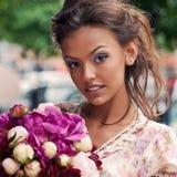 Una bella ragazza in vestito da estate con un mazzo di fiori i Fotografie Stock Libere da Diritti