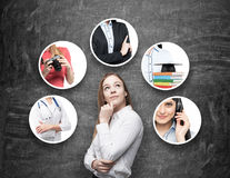 Una bella signora in una camicia convenzionale sta pensando alle professioni differenti Lavagna nera come fondo immagine stock