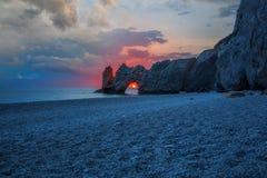 Una bella spiaggia ad alba con il sole nel foro delle rocce immagine stock libera da diritti