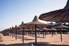 Una bella spiaggia sabbiosa ad una località di soggiorno con i parasoli Immagini Stock Libere da Diritti
