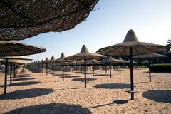 Una bella spiaggia sabbiosa ad una località di soggiorno con i parasoli Fotografia Stock Libera da Diritti