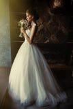 Una bella sposa sta stando in una stanza nella finestra di una finestra Immagini Stock Libere da Diritti