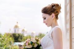Una bella sposa su un giorno delle nozze con un mazzo a disposizione contro lo sfondo di una chiesa cristiana ortodossa immagini stock libere da diritti