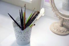 Una bella, tazza bianca con i modelli openwork per la conservazione delle spazzole per compone fotografie stock libere da diritti