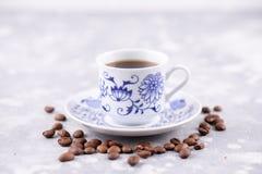 Una bella tazza di caffè della porcellana con caffè nero caldo Chicchi di caffè sparsi intorno ai precedenti Porcellana d'annata  Immagini Stock Libere da Diritti