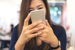 Una bella tenuta asiatica della donna di affari, utilizzando ed esaminando Smart Phone nel caffè moderno fotografie stock