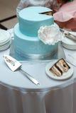 Una bella torta nunziale blu sta taglianda dalle persone appena sposate Immagine Stock Libera da Diritti