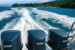 Una bella traccia spumosa da una barca con tre motori potenti, andanti dalla spiaggia della banana di Coral Koh He Island, tailan fotografia stock