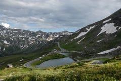 Una bella vista del lago, del prato e di più alta strada sorta della montagna in Austria - strada alpina di Grossglockner alta Immagini Stock Libere da Diritti
