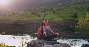 In una bella vista della natura con un lago e le signore verdi del campo due facendo le pose di meditazione sulle grandi pietre e video d archivio
