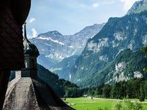 Una bella vista di estate di vecchia cupola del ` s della chiesa, della valle verde e della catena montuosa delle alpi a Engelber Immagine Stock