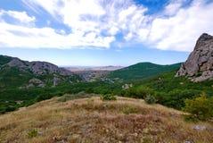 Una bella zona di montagna con gli alberi verdi, l'erba gialla, le rocce grige ed il cielo blu Fotografie Stock