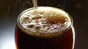 Una bevanda di coca-cola è versata in un vetro Bolle della bevanda gassosa video d archivio