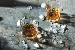 Una bevanda e un ghiaccio dell'alcool Whiskey con i pezzi di ghiaccio Vetri con una forte bevanda immagine stock