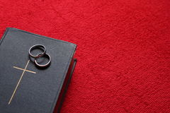 Una biblia con los anillos de bodas en fondo rojo Fotos de archivo