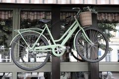 Una bicicleta clásica con las flores en la cesta, colgando fuera de una ventana imagen de archivo