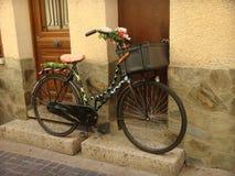 Una bicicleta excavada adornada delante de una casa Fotografía de archivo