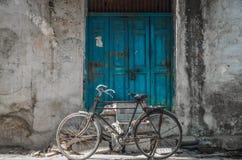 Una bicicleta vieja parqueó afuera delante de un a puerta cerrada de madera azul del viejo vintage de una casa vieja en Jodhpur,  imágenes de archivo libres de regalías