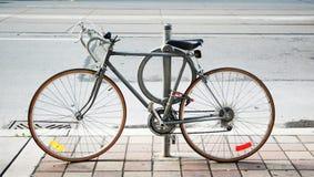 Una bicicletta bloccata su sulla via Fotografie Stock Libere da Diritti